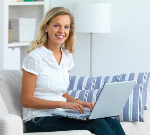 Young woman sitting on sofa and using a laptop